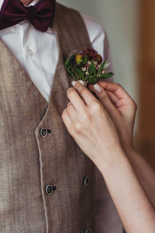 Las manos delicadas del ` s de la novia ajustan boutonniere del ` s del novio foto de archivo