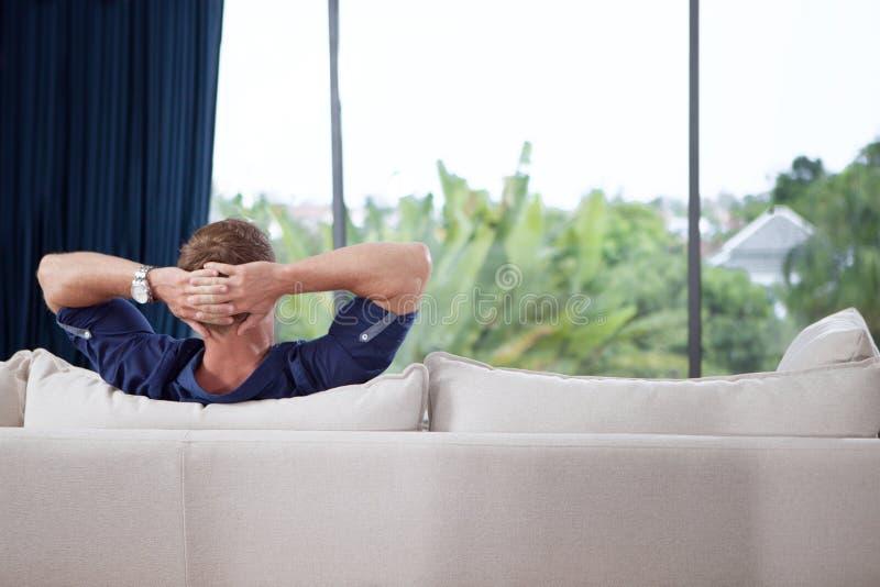 las manos detrás de su cabeza son relajantes en el sofá imagen de archivo