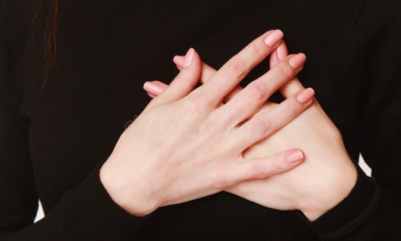 Las manos doblaron en el pecho como símbolo del la del cuerpo de las sensaciones duras fotografía de archivo