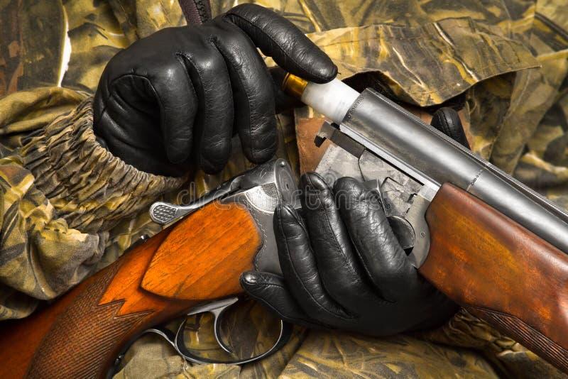 Las manos en guantes cargan la escopeta fotografía de archivo libre de regalías