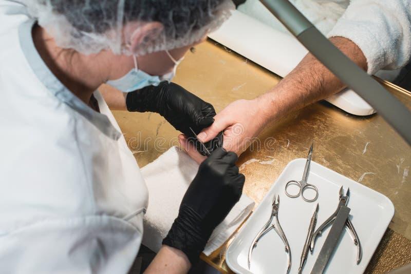 Las manos en guantes cuidan sobre clavos de la mano del ` s del hombre Salón de belleza de la manicura Limadura de clavos con el  foto de archivo libre de regalías