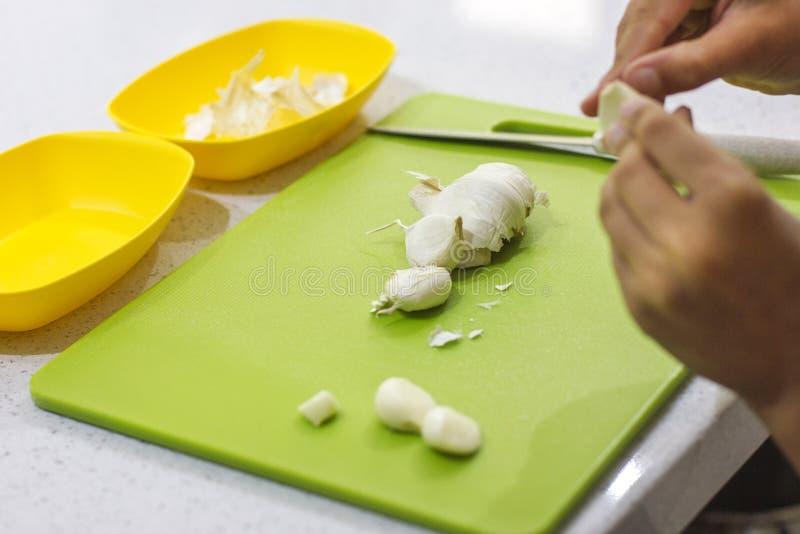 Las manos están cortando el ajo fresco en un tablero verde en la cocina fotos de archivo libres de regalías