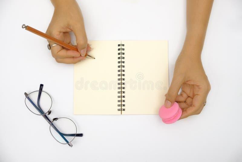 Las manos están escribiendo en el libro imagenes de archivo