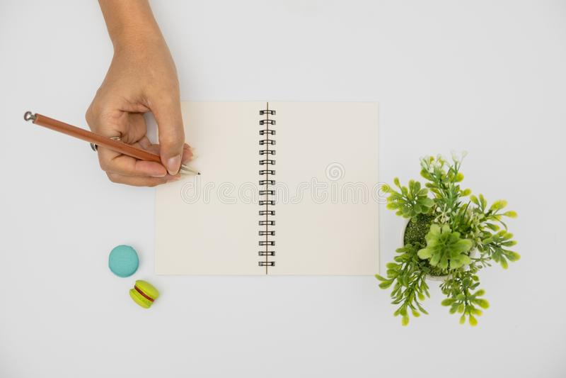 Las manos están escribiendo en el libro imagen de archivo