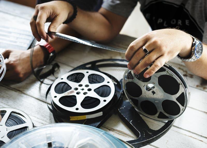 Las manos están llevando a cabo una tira de la película imagen de archivo