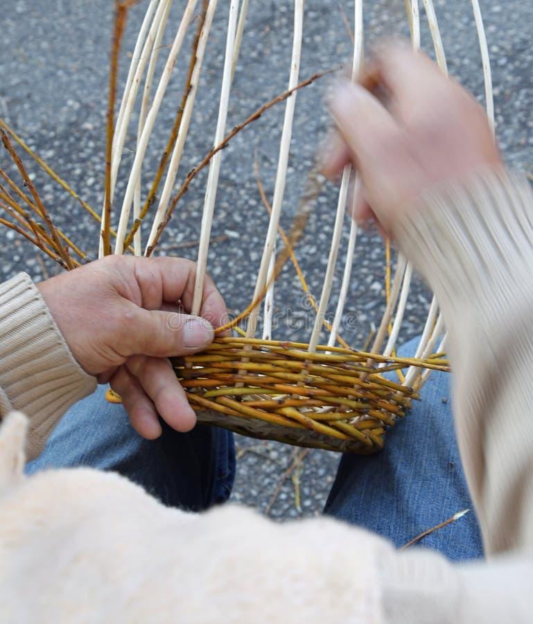 Las manos expertas del artesano mayor crean bas de mimbre tejidos foto de archivo