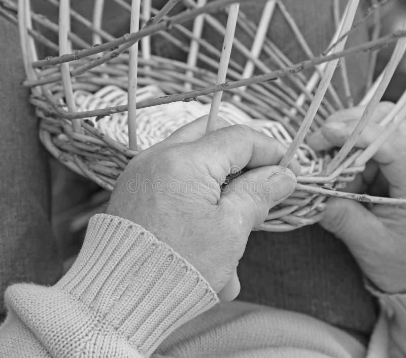 Las manos expertas del artesano mayor crean una cesta de mimbre foto de archivo