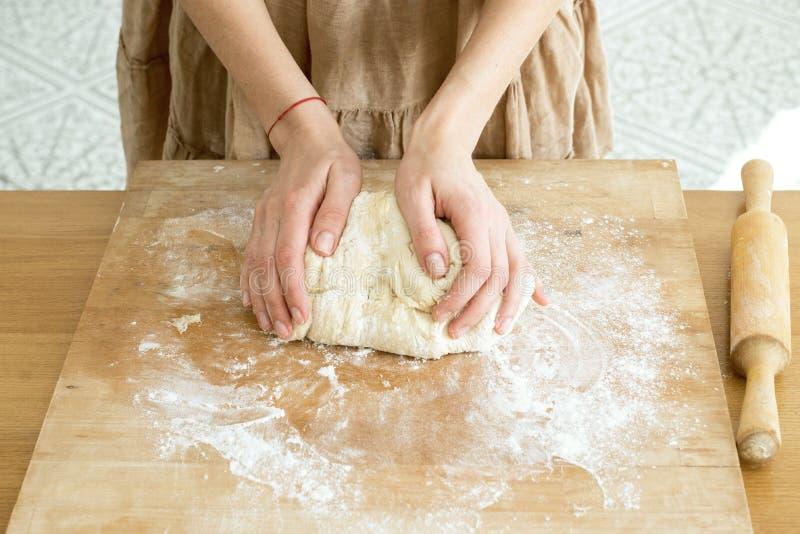 Las manos femeninas amasan la pasta en un tablero de madera que cocina la hornada foto de archivo