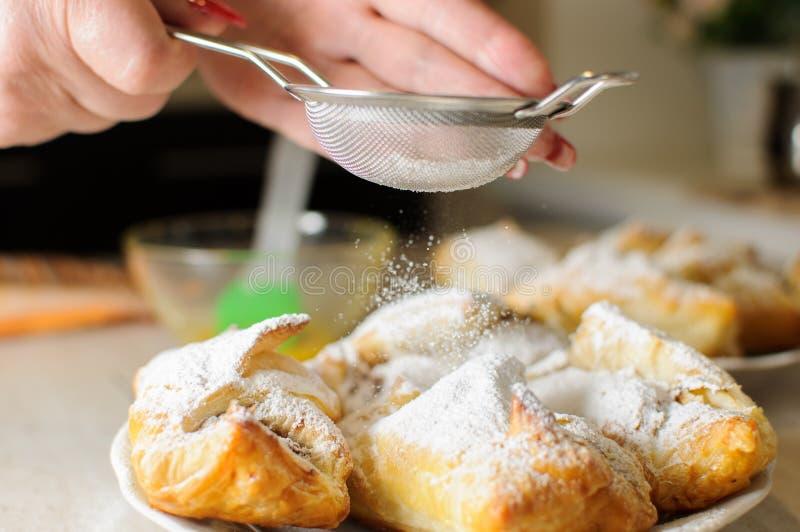 Las manos femeninas asperjan el azúcar en polvo en soplos de la manzana imagen de archivo