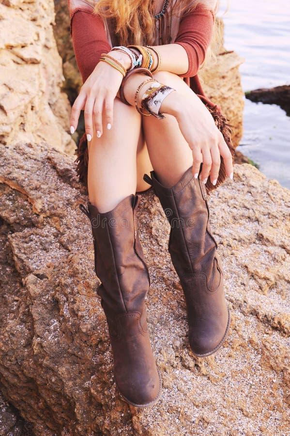 Las manos femeninas con la manicura blanca y las pulseras elegantes y las piernas del boho se vistieron en las botas de cuero imagen de archivo libre de regalías