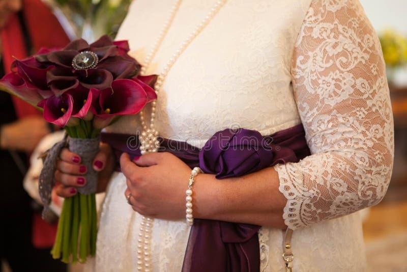 Las manos femeninas con un ramo de Borgoña florecen fotografía de archivo