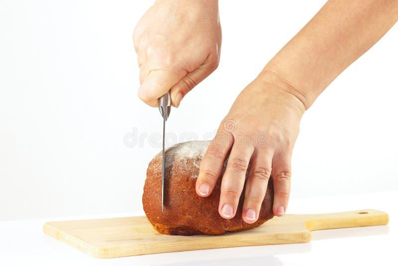 Las manos femeninas cortaron el pan de centeno en una tabla de cortar fotografía de archivo