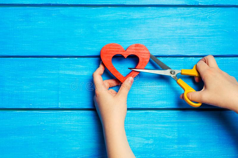 Las manos femeninas cortaron un corazón rojo de madera con las tijeras en un fondo azul El concepto de romper las relaciones, pel imagen de archivo libre de regalías