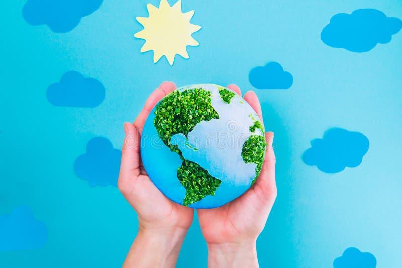 Las manos femeninas de la visión superior que llevan a cabo el papel de la tierra y el collage de los brotes del verde modelan en foto de archivo libre de regalías