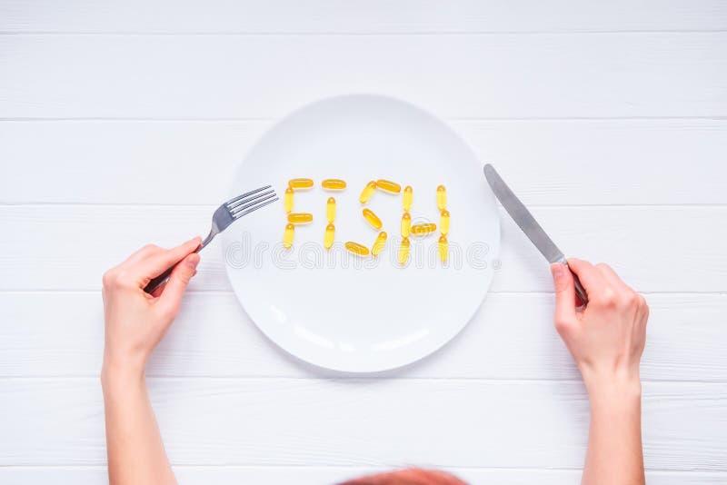 Las manos femeninas de la visión superior que sostienen el cuchillo y la bifurcación debajo de la placa redonda con los pescados  imagenes de archivo