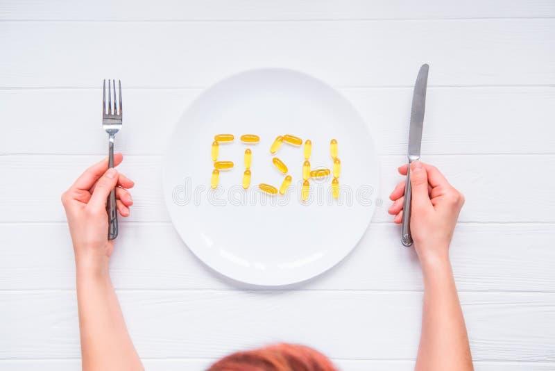 Las manos femeninas de la visión superior que sostienen el cuchillo y la bifurcación debajo de la placa redonda con los pescados  imagen de archivo