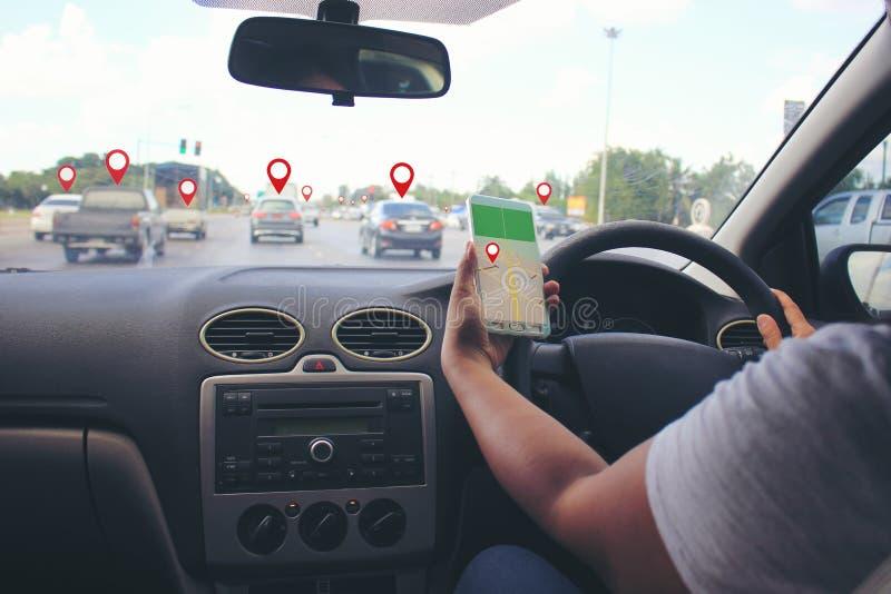 Las manos femeninas del conductor que sostienen el panel de la dirección del coche con sostener el smartphone para comprobar la n imagen de archivo