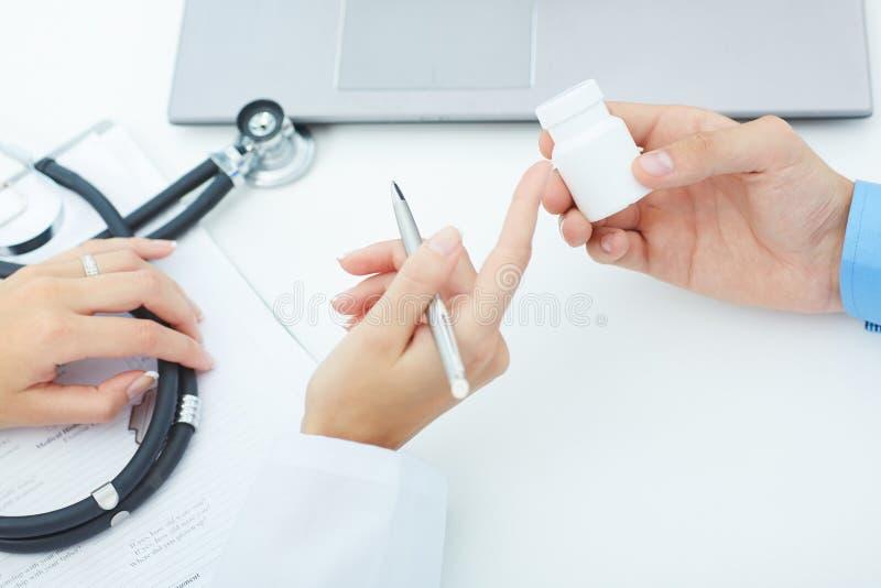 Las manos femeninas del doctor de la medicina sostienen el tarro de píldoras y explican al paciente cómo utilizar la dosis diaria fotografía de archivo libre de regalías
