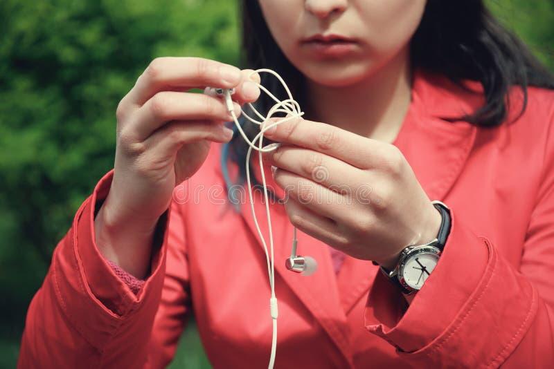 Las manos femeninas desenredan los peque?os auriculares blancos al aire libre fotos de archivo