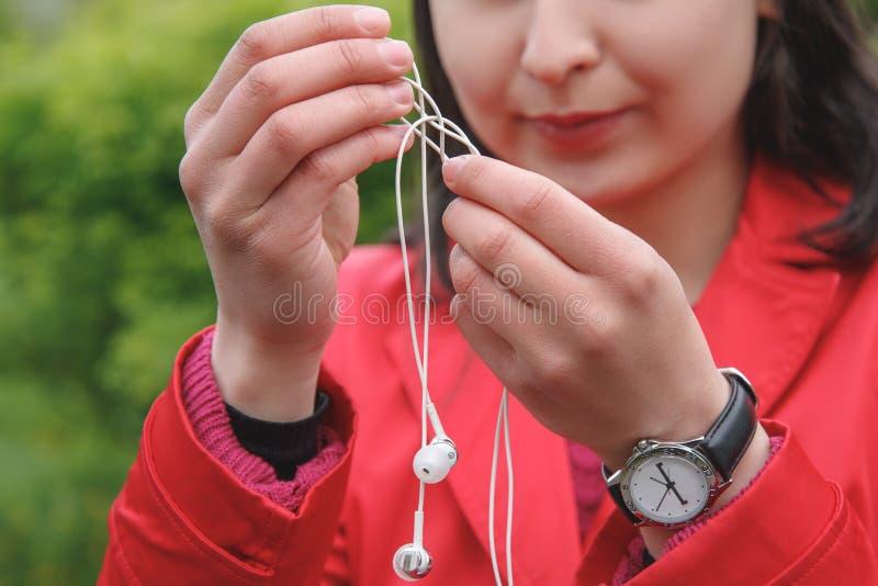 Las manos femeninas desenredan los peque?os auriculares blancos al aire libre fotos de archivo libres de regalías