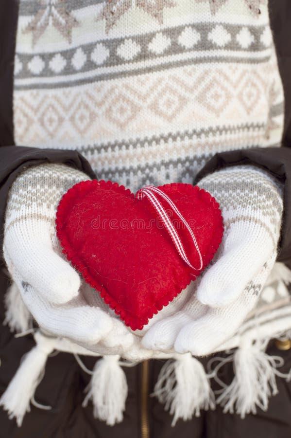 Las manos femeninas en blanco hicieron punto las manoplas con el corazón rojo romántico fotos de archivo libres de regalías