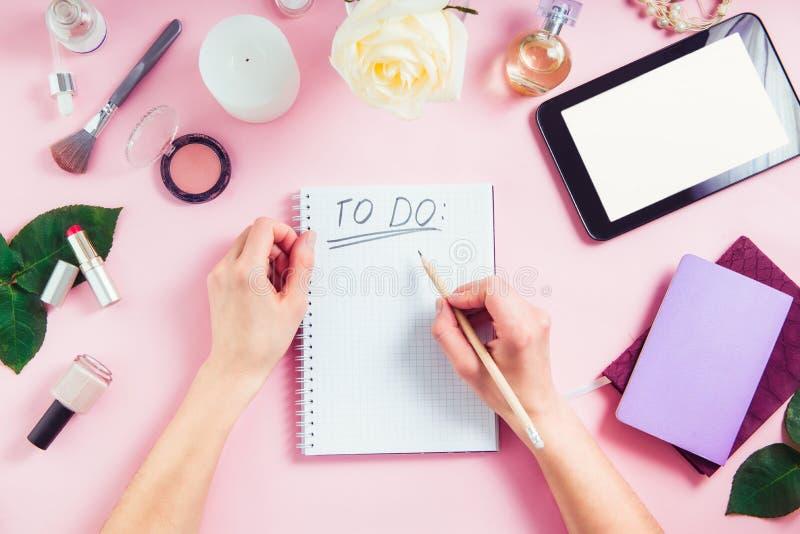 Las manos femeninas escriben para hacer la lista en el fondo rosado con los cosméticos, taza de café, cuadernos, tableta con la p fotos de archivo