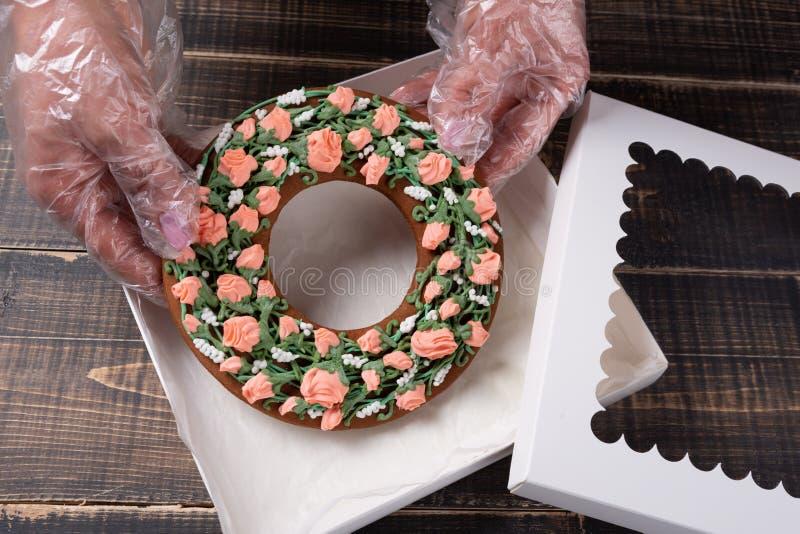 Las manos femeninas están embalando el pan de jengibre del regalo en una caja, en viejos tableros, el concepto de un día de fiest foto de archivo