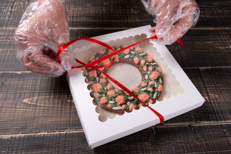 Las manos femeninas están embalando el pan de jengibre redondo en la caja, concepto del regalo, contra la perspectiva de tableros imágenes de archivo libres de regalías