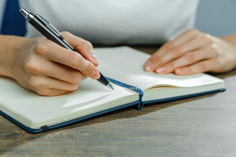 Las manos femeninas están escribiendo en un cuaderno fotos de archivo