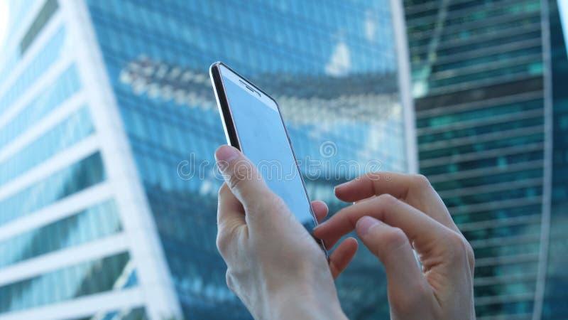 Las manos femeninas están utilizando un smartphone contra la perspectiva de centros de negocios de cristal grandes, primer foto de archivo