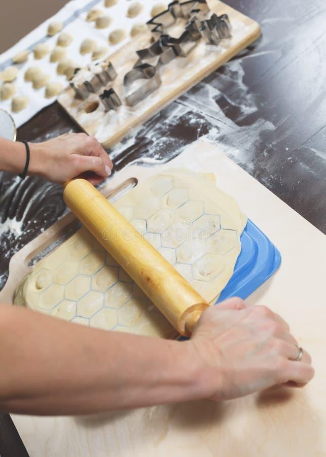 Las manos femeninas hacen con amor las bolas de masa hervida en casa para poseer día de fiesta de la familia imagenes de archivo