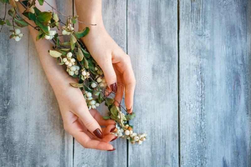 Las manos femeninas hermosas mienten con las flores en el fondo de madera, cuidado de piel de la mano, manicura hermosa imagenes de archivo