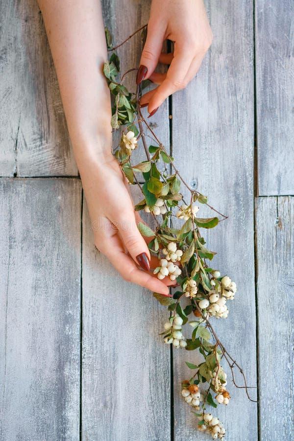 Las manos femeninas hermosas mienten con las flores en el fondo de madera, cuidado de piel de la mano, manicura hermosa imagen de archivo libre de regalías