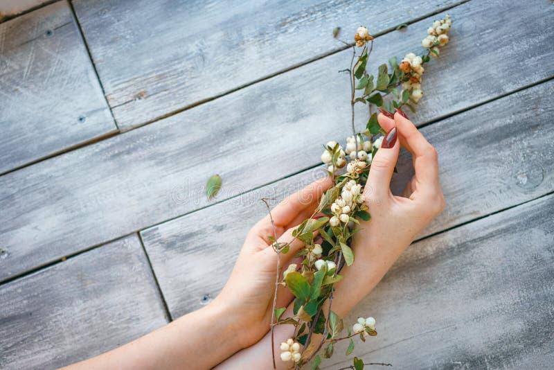 Las manos femeninas hermosas mienten con las flores en el fondo de madera, cuidado de piel de la mano, manicura hermosa fotos de archivo