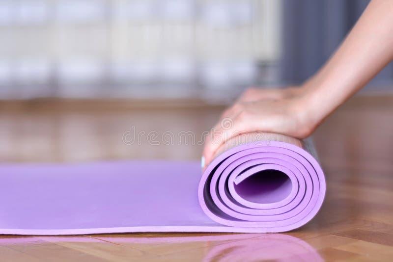 Las manos femeninas jovenes ruedan la estera púrpura de la yoga o de la aptitud en piso de entarimado fotografía de archivo