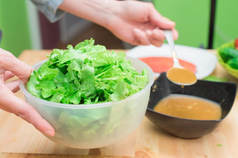 Las manos femeninas que añaden la salsa a la lechuga de lechuga se van Cocina casera Alimento sano y sano sabroso fotos de archivo