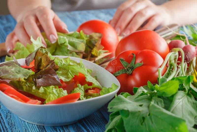 Las manos femeninas que añaden lechuga se van en el cuenco con la ensalada, cierre-u imagenes de archivo