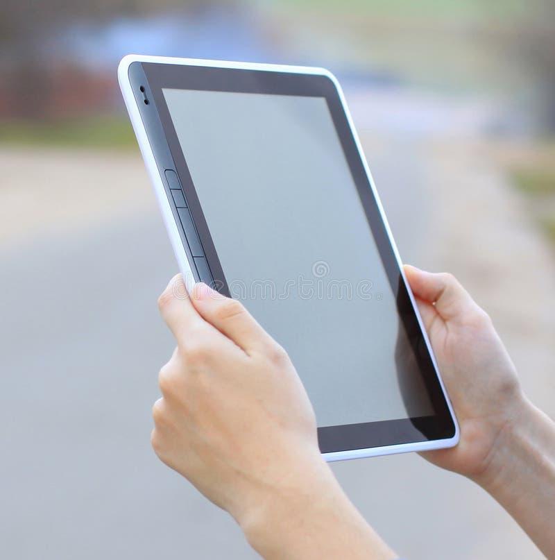 Las manos femeninas que sostienen una tableta tocan el artilugio del ordenador con la pantalla aislada imágenes de archivo libres de regalías
