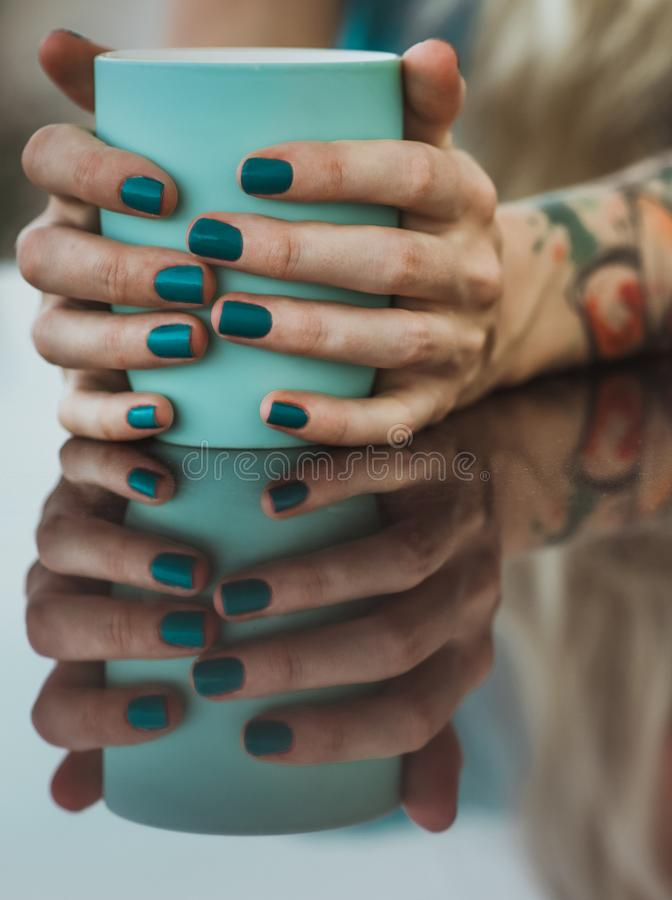Las manos femeninas se cierran encima de sostener la taza de la turquesa La reflexión en la tabla cenando en el aire abierto, la  fotos de archivo