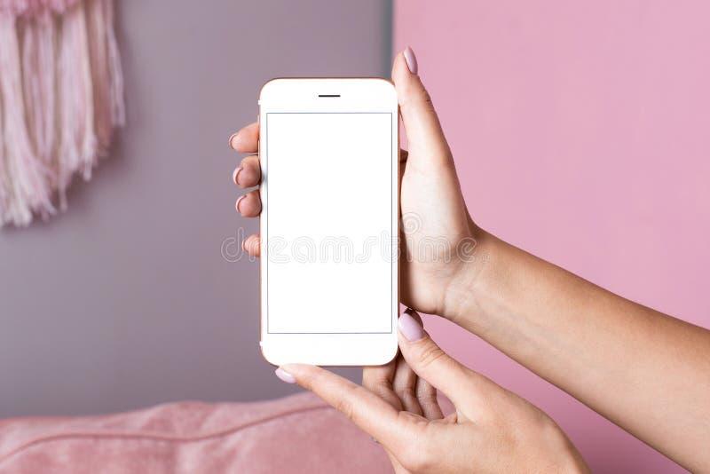 Las manos femeninas sostienen el tel?fono m?vil con la mofa blanca de la pantalla para arriba en un fondo interior rosado fotografía de archivo libre de regalías