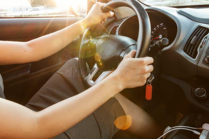 Las manos femeninas sostienen el volante, primer Una mujer está conduciendo un coche entonado fotografía de archivo libre de regalías