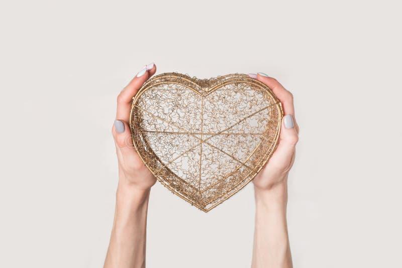 Las manos femeninas sostienen la caja transparente del alambre de metal en la forma de un aislante del corazón en el fondo blanc fotografía de archivo libre de regalías