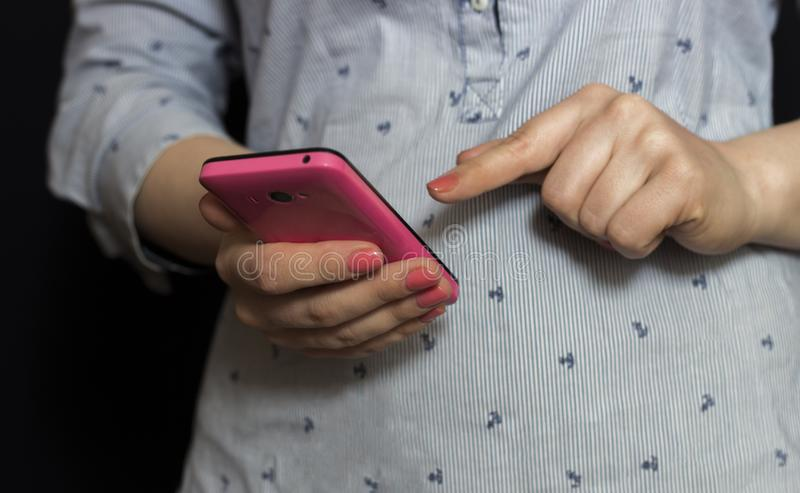 Las manos femeninas sostienen un smartphone rosado en sus manos La muchacha funciona con su finger en el teléfono imagen de archivo libre de regalías