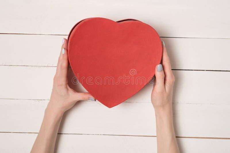 Las manos femeninas sostienen una caja en forma de coraz?n roja contra la perspectiva de una tabla de madera blanca foto de archivo libre de regalías