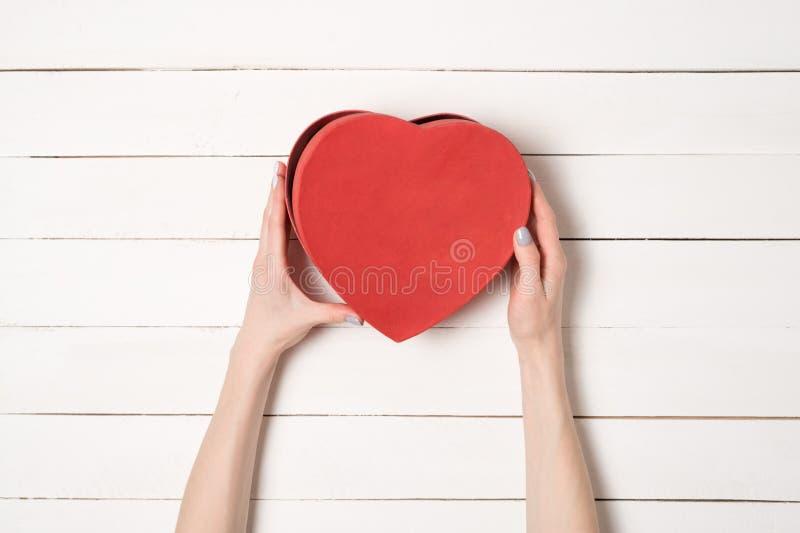 Las manos femeninas sostienen una caja en forma de coraz?n roja contra la perspectiva de una tabla de madera blanca fotografía de archivo libre de regalías