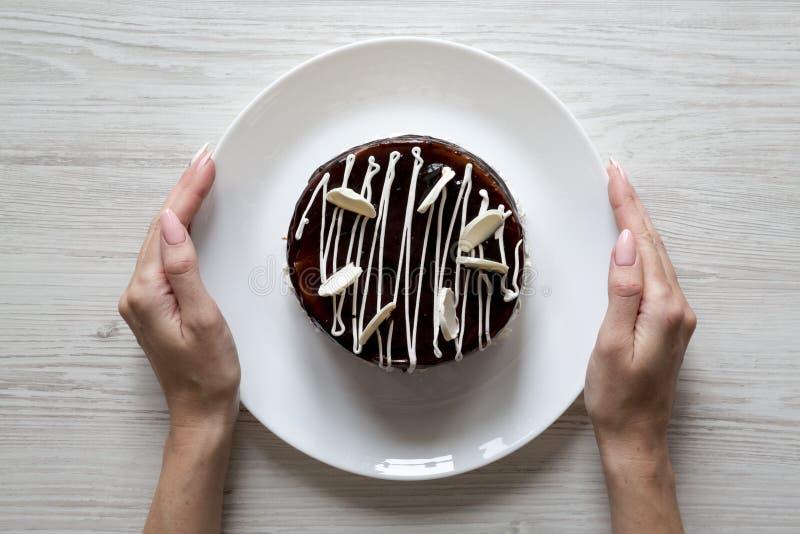 Las manos femeninas sostienen una placa con la torta hecha en casa de la cereza del chocolate sobre el fondo de madera blanco, vi fotografía de archivo libre de regalías