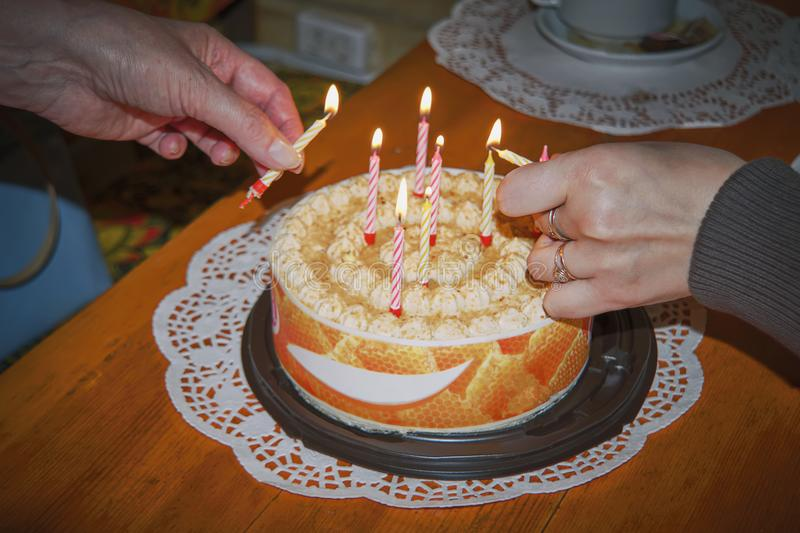 Las manos femeninas sostienen una torta festiva imagenes de archivo
