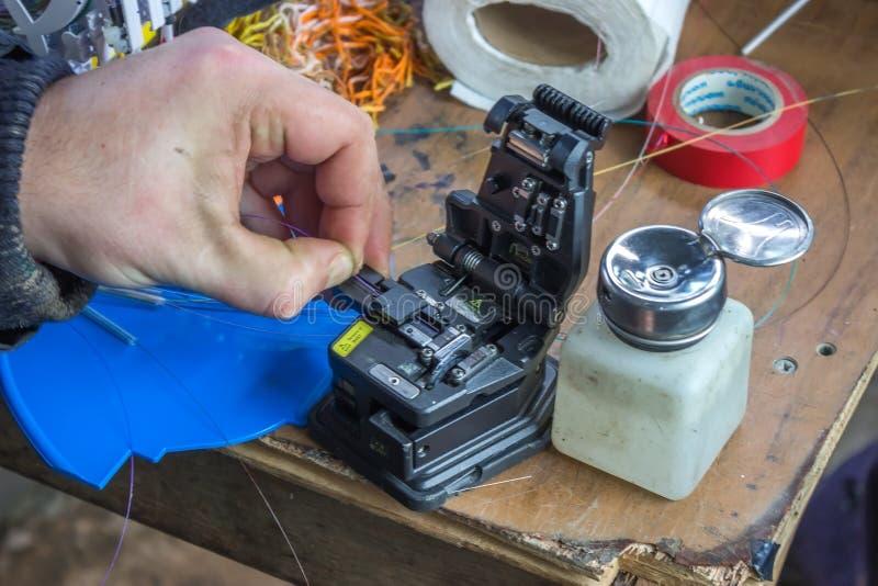 Las manos fibroópticas del técnico hienden la fibra 2 imagen de archivo libre de regalías