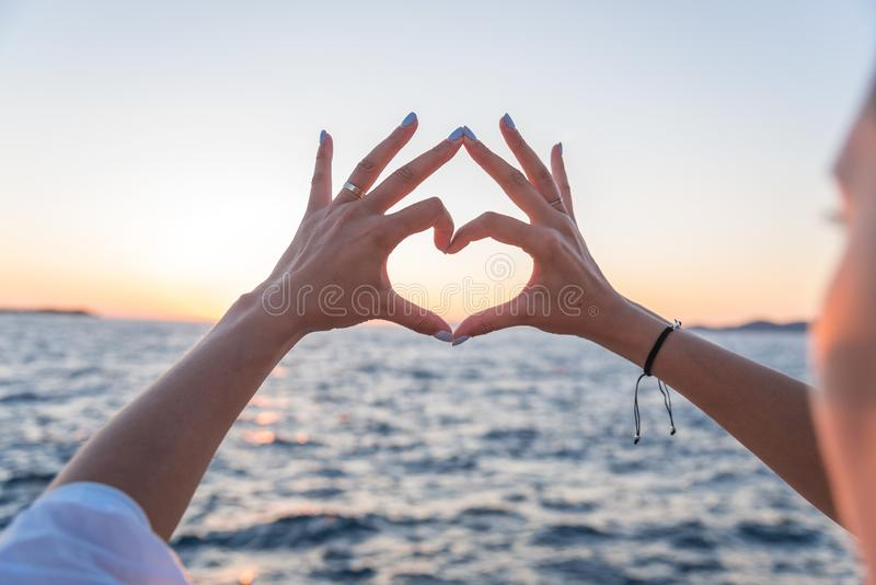 Las manos hermosas femeninas jovenes en el fondo del mar muestran el símbolo del corazón Vacaciones - concepto imagen de archivo libre de regalías