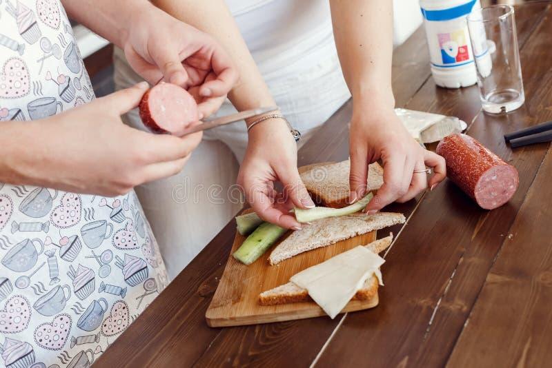Las manos humanas hombre y mujer se cortan en el salami, queso Closep, haciendo los bocadillos fotos de archivo